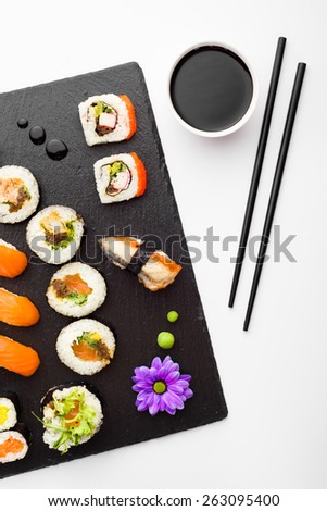 Sushi, chopsticks and soy sauce on black stone plate top view - stock photo