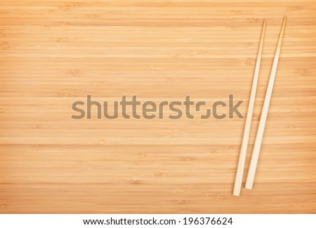 Sushi chopsticks on bamboo table with copy space - stock photo