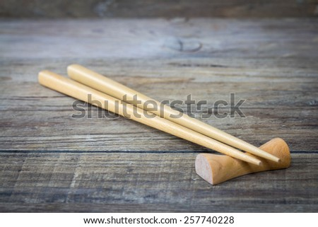 Sushi chopsticks on wood background. - stock photo