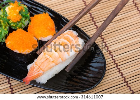 sushi in black dish on wooden background