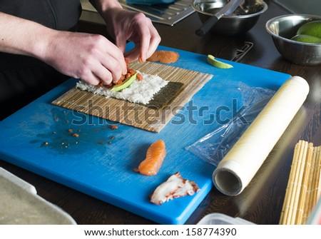 Sushi in sushi bar. Sushi making.Hands rolling sushi - stock photo