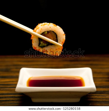 sushi keep chopsticks and dipped into the sauce - stock photo