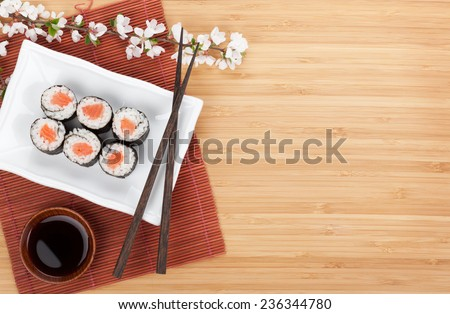 Sushi maki with salmon and sakura branch over bamboo table - stock photo