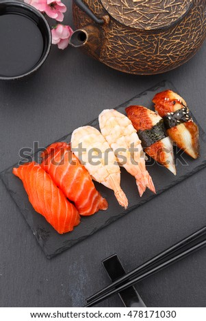 Sushi nigiri set on a stone plate over black background