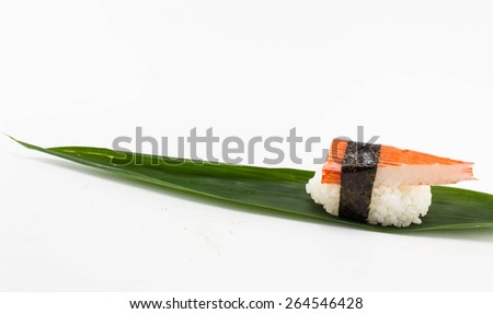 Sushi on bamboo leaves on a white background.