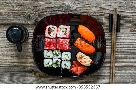 sushi on plate with chopsticks on wooden background