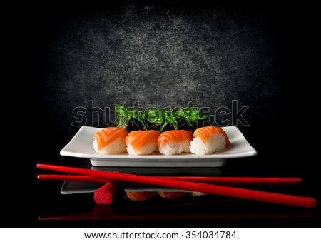 Sushi on plate with red chopsticks on black background