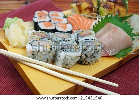 Sushi Plate. Japanese sushi plate with salmon and yellow tail snapper sashimi, salmon roll, scallop roll and chopsticks on a stylish wood serving board.  - stock photo
