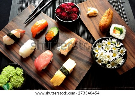 Sushi plate with small chrysanthemums - stock photo