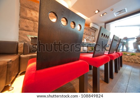Sushi restaurant  with red chairs, focus on chairs