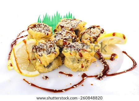 sushi roll fried in tempura batter with sauce - stock photo