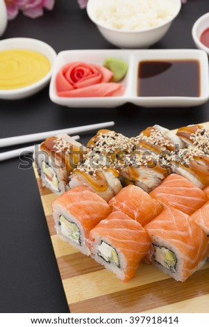 Sushi roll on a wooden plate ( gete ) with sauces ginger and wasabi over black background