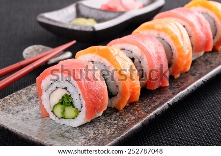 Sushi roll : Row of salmon & tuna sushi rolls with chopsticks - stock photo