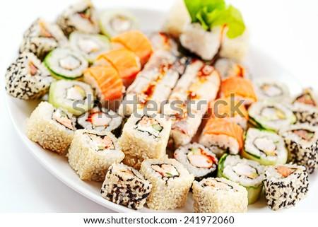 Sushi roll set on a white dish. Different japanese food. Tempura, sesame, salmon, eel. Selective focus. - stock photo