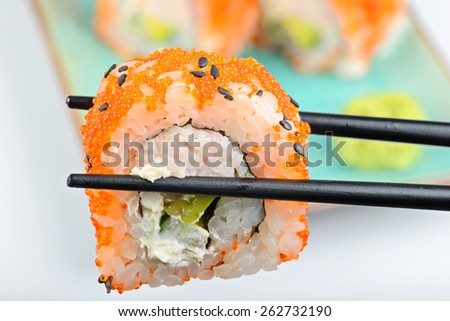 Sushi roll with black chopsticks and other rolls on the background - stock photo