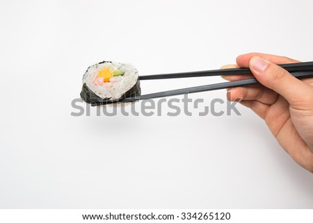 Sushi roll with black chopsticks isolated on white background.