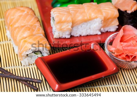 Sushi roll with salmon and shrimp tempura on wooden table