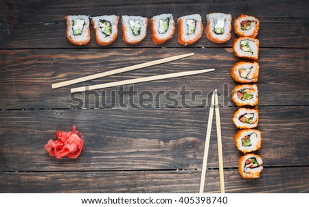 Sushi roll with salmon on wood background. Top view.  - stock photo