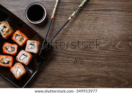 Sushi roll with salmon over wood background