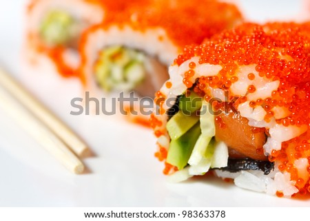 Sushi Roll with tobiko caviar, salmon, avocado and cucumber close-up