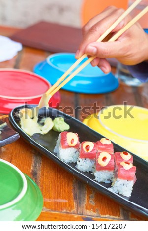 Sushi roll with tuna, avocado, spicy mayo, ginger, wasabi surrounded by colorful plating.