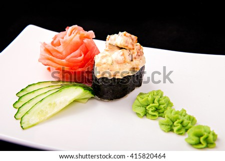 Sushi roll with wasabi, ginger and cucumber on white plate - stock photo