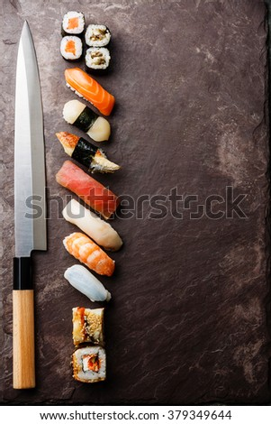 Sushi rolls and nigiri with Japanese knife on stone slate background - stock photo