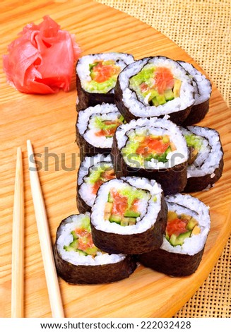 sushi, rolls, ginger and chopstick on bamboo mat - stock photo