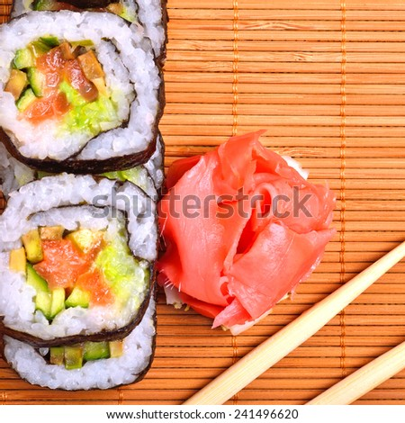 sushi, rolls, ginger and chopstick on bamboo mat