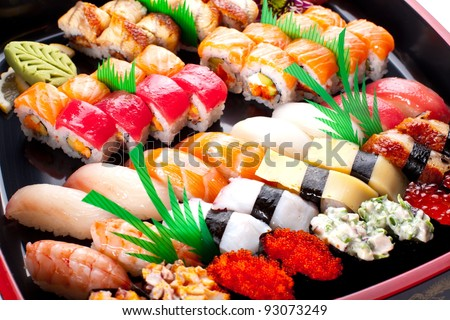 Sushi rolls on a black plate. - stock photo