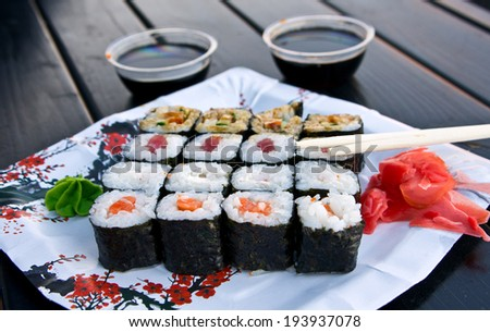 Sushi rolls on a platter with soy sauce, wasabi and pickled ginger. The atmosphere in the evening cafe helps to understand the Japanese flavor. Russia Kaluga City. - stock photo