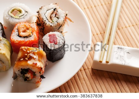 Sushi rolls on a white plate with chopsticks on a white stand, closeup - stock photo