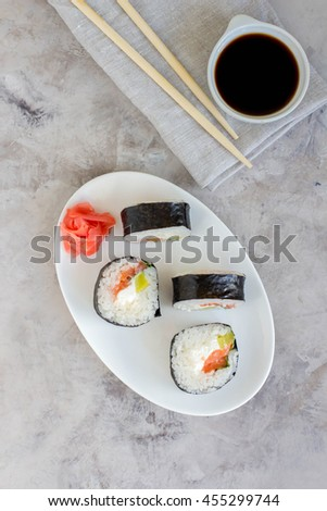 Sushi rolls on white plate on gray table. Traditional Asian food. Diet healthy food. Top view - stock photo