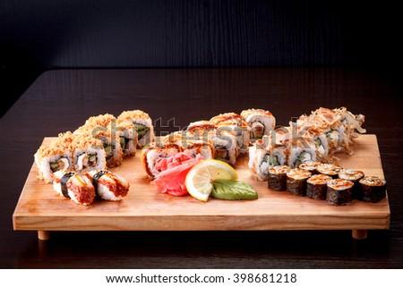sushi, rolls, plate, horizontal photo on a dark background  - stock photo