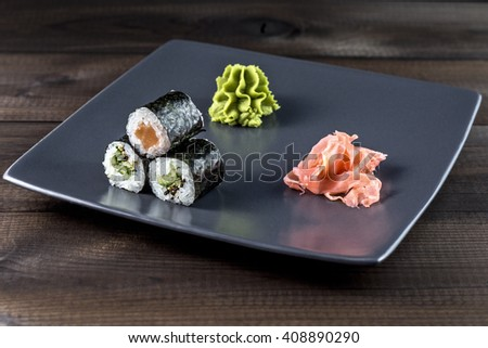 Sushi rolls set. Kappamaki and Sakemaki with pickled ginger and wasabi served on grey plate. - stock photo