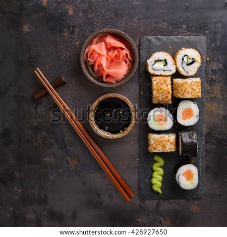 Sushi rolls set with marinated ginger, soy sauce and wasabi on stone background, selective focus