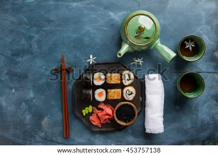 Sushi rolls set with marinated ginger, soy sauce, wasabi and green tea  on stone background, selective focus - stock photo
