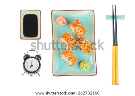 Sushi rolls with masago, served on turquoise plate with pickled ginger, soy sauce and chopsticks over isolated white background. Top view. Time to eat concept. - stock photo