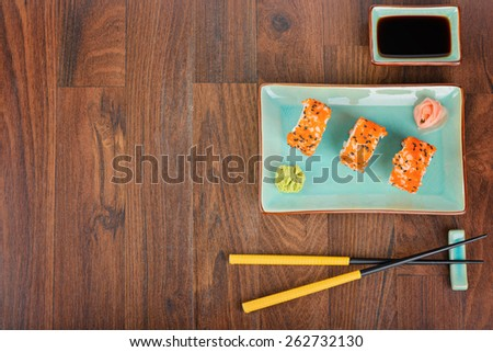 Sushi rolls with masago, served on turquoise plate with pickled ginger, soy sauce and chopsticks on wooden table. Top view. - stock photo