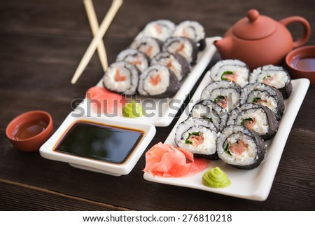 Sushi rolls with salmon on white plate - stock photo