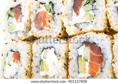 Sushi rolls with sesame seeds on the white background