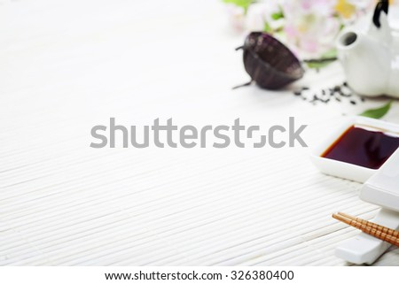 Sushi set, green tea and sakura branch on bamboo mat - stock photo