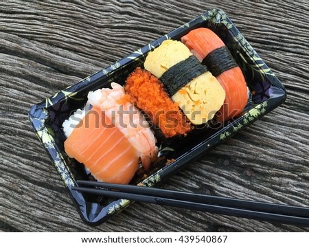 Sushi set in black plate and chopstick on wood background