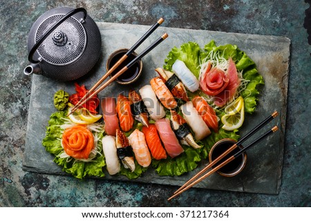 Sushi Set nigiri and sashimi with tea served on gray stone slate on metal background - stock photo