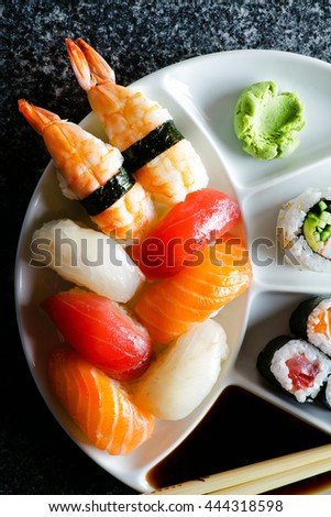 Sushi Set nigiri and sushi rolls served on black marble slat