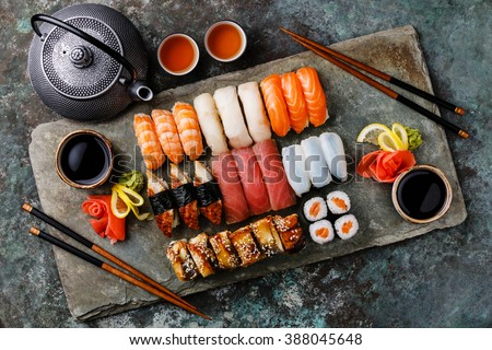 Sushi Set nigiri and sushi rolls with tea served for two on gray stone slate on metal background - stock photo