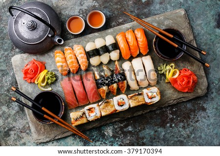 Sushi Set nigiri and sushi rolls with tea served on gray stone slate on metal background - stock photo