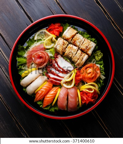 Sushi Set nigiri, rolls and sashimi served in traditional Japan black Sushioke round plate - stock photo
