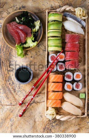 Sushi set nigiri, sashimi and rolls on clay plate served with chopsticks and soy sauce on stone surface. Flat lay.  - stock photo