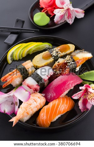 Sushi set on a black plate and black background